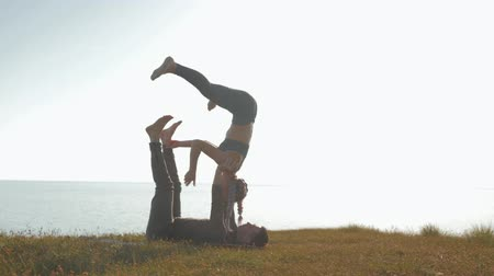 meditující : acro yoga outdoors, girl in sports suit is balancing on the legs and hands of her male partner at the meadow on background of sea and sky