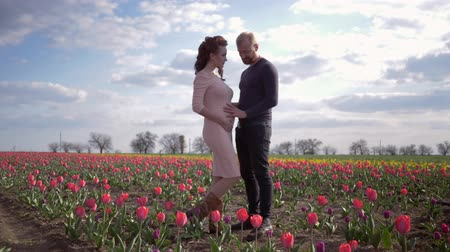 csöves virág : happy expectant family, young couple waiting of baby touching stomach and take pleasure vacation on flowers tulip lawn against clear sky