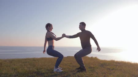 fonat : active lifestyle, athletic couple together holding hands and simultaneously crouching in sunshine at nature Stock mozgókép