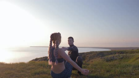 pigtail : healthy lifestyle, couple athletic young woman and man holding hands and simultaneously crouching in sunlight at nature Stock Footage