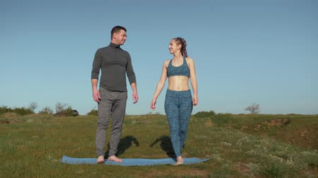 pigtailler : healthy lifestyle, couple relaxes before training in the fresh air while standing on the sports mat holding hands on background of sky with birds