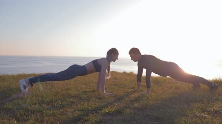 косички : outdoor exercise, sports couple in love simultaneously doing push-ups during sunset on a mountain against a beautiful landscape Стоковые видеозаписи