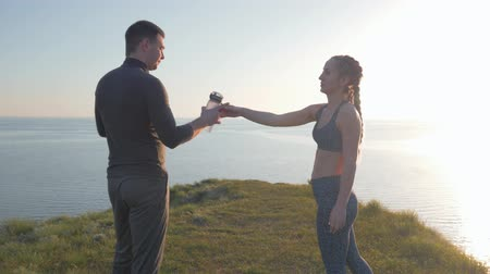 шейкер : fitness outdoors, sportswoman gives male shaker with drinking mineral water after cardio training on nature in bright sunshine on sea cliff