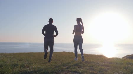 body building : happy sportswoman jumps on male and whirls on green lawn on river cliff in bright sunshine after running and cardio training on nature