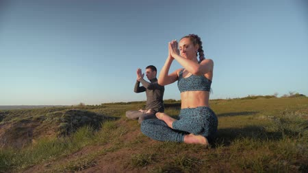 pigtailler : yoga hobby, athletic couple together on mountain peak meditating in lotus position on background of blue sky Stok Video