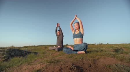 pigtailler : yoga religion, sports pair together meditating in lotus position on meadow on background of blue sky