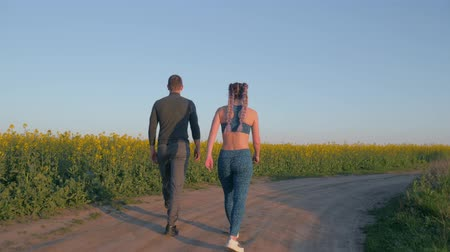 csöves virág : sports leisure, young couple girl and boy with kanekalon braids and athletic body walking in blooming rapeseed field against blue clear sky