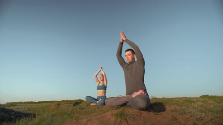 pigtailler : yoga therapy, athletic woman and man together meditating in lotus position on the mountain peak on background of blue sky