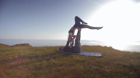 open sky : yoga, athletic female acrobat is balancing on the legs and hands of her male partner in sunlight on background of sky and the sea on the mountain