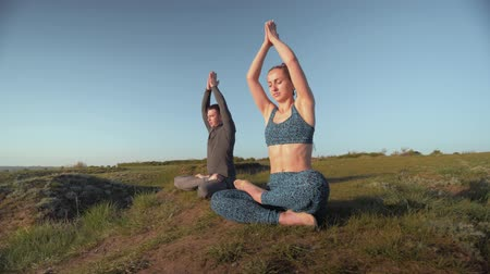pigtailler : yoga lifestyle, sporting woman and man on meadow together meditating in lotus position on background of blue sky