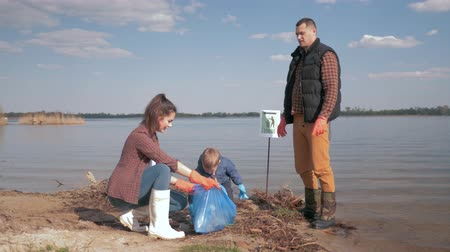 coletando : environmental protection, young woman and man volunteers with kid boy collect plastic and polyethylene trash on dirty embankment near water Stock Footage