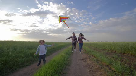 idílio : cheerful little boy with a kite in hands runs near young parents in slow motion on countryside during active weekend in the open air