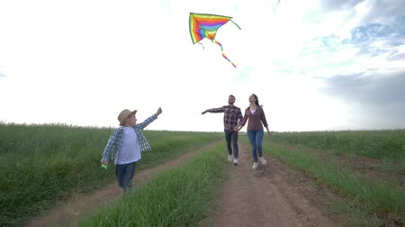 idílio : family idyll, little boy with a kite in his hands runs on countryside in slow motion on background of young parents and sunny sky during weekend at nature