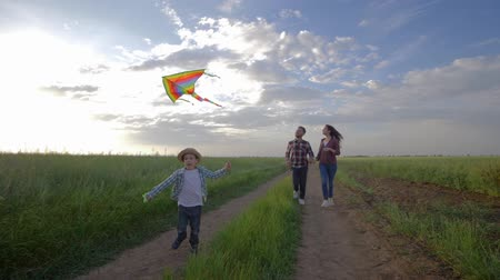 idílio : happy active family weekend, little boy with a kite in hands runs near young parents in slow motion on countryside in the open air