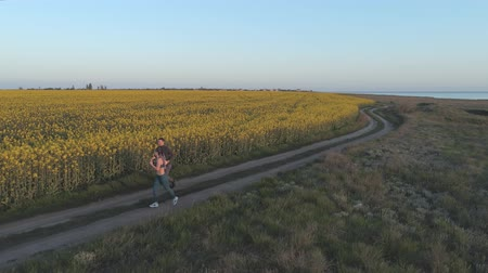 csöves virág : jog outdoors, young sports man and woman run along road near rapeseed blooming meadow during cardio training in nature, top view