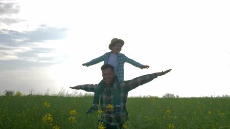 idílio : father and son walking on meadow, child sits on shoulders dad and play airplane with arms raised on rapeseed field on background sky in slow motion