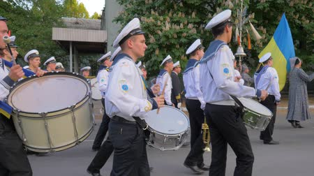 ドラムスティック : KHERSON, UKRAINE - MAY 20, 2019: Festival Melpomene of Tavria, marching band on parade, young sailors in white uniform play on big drums and carry Ukrainian flag at the street in slow motion
