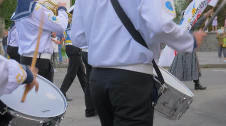 dobos : KHERSON, UKRAINE - MAY 20, 2019: Festival Melpomene of Tavria, marching band, drummers sailors with sticks in hands close-up play on big drums during the parade in the street