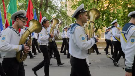 trombeta : KHERSON, UKRAINE - MAY 20, 2019: Festival Melpomene of Tavria, Marine Academy band marching in a parade, students in uniform play on musical instruments and carry colorful flags