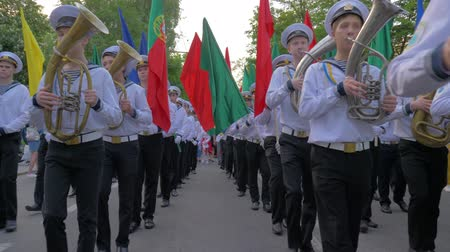 haditengerészeti : KHERSON, UKRAINE - MAY 20, 2019: Festival Melpomene of Tavria, sailors of Marine Academy in uniform play on musical instruments during the march and carry colorful flags on parade at the street Stock mozgókép