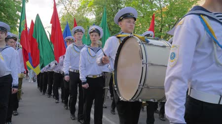 haditengerészeti : KHERSON, UKRAINE - MAY 20, 2019: Festival Melpomene of Tavria, students of Marine Academy march on a parade with multicolored flags in their hands, a young sailor with sticks close-up beats the big drum