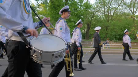 моряк : KHERSON, UKRAINE - MAY 20, 2019: Festival Melpomene of Tavria, parade at the street, sailors in uniform play on musical instruments during the march carry colorful flags