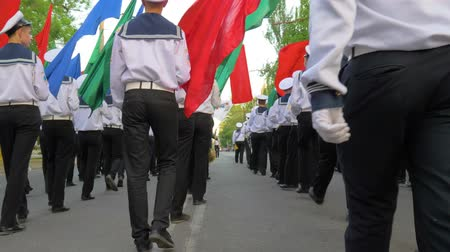 denizciler : KHERSON, UKRAINE - MAY 20, 2019: Festival Melpomene of Tavria, young sailors in white uniform on parade marching with multicolored flags in the street Stok Video