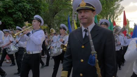 моряк : KHERSON, UKRAINE - MAY 20, 2019: Festival Melpomene of Tavria, sailors play musical instruments and carry colored flags on the street during the parade