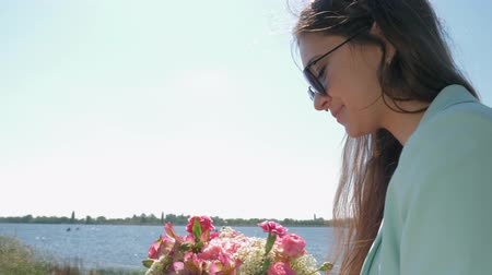 csöves virág : merry florist woman in sunglasses collects beautiful bouquet of pink flowers on nature close up