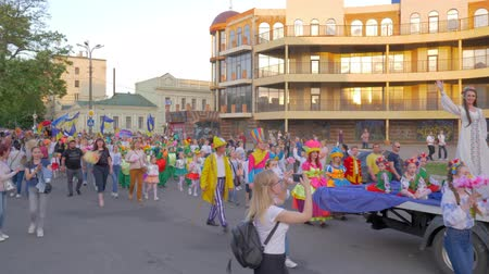 festividades : KHERSON, UKRAINE - MAY 20, 2019: Festival Melpomene of Tavria, city holiday, many people in different costumes walk along city street behind chariot with beautiful woman in dress and shout chants on open air
