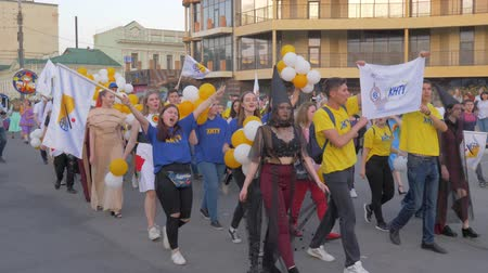 festividades : KHERSON, UKRAINE - MAY 20, 2019: Festival Melpomene of Tavria, city traditions, crowd youth in different costumes with balloons walk along city street and shout chants on open air