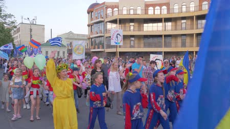 festividades : KHERSON, UKRAINE - MAY 20, 2019: Festival Melpomene of Tavria, crowd of adults and children in suits with flags in hands are walking along city street during festive festival Vídeos