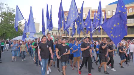 festividades : KHERSON, UKRAINE - MAY 20, 2019: Festival Melpomene of Tavria, crowd of people with lots of EU flags are walking along city street