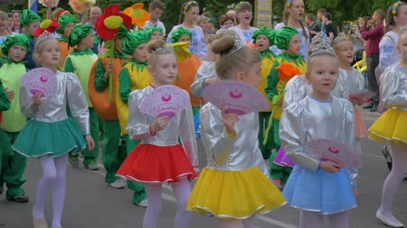 festividades : KHERSON, UKRAINE - MAY 20, 2019: Festival Melpomene of Tavria, festivity parade, crowd of children in different costumes walk along city street and shout chants outdoors