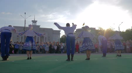 festividades : KHERSON, UKRAINE - MAY 20, 2019: Festival Melpomene of Tavria, Folk Festivities, young boys and girls in national costumes dance hopak into city square before crowd people on holiday Vídeos