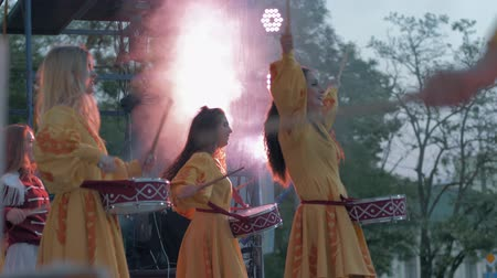 buben : KHERSON, UKRAINE - MAY 20, 2019: Festival Melpomene of Tavria, Folklore Festival, group girls drummers beat drum sticks on musical instrument close-up on festive show on street