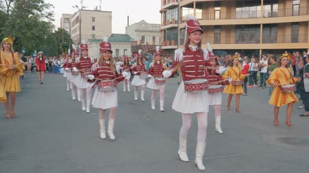 folk holiday : KHERSON, UKRAINE - MAY 20, 2019: Festival Melpomene of Tavria, Street performance of festive march of drummers girls in costumes on city street in holiday festival