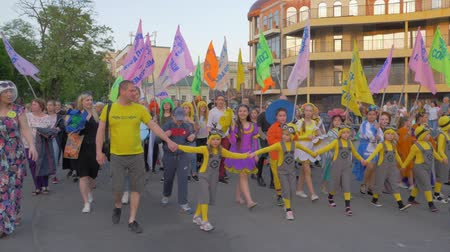 festividades : KHERSON, UKRAINE - MAY 20, 2019: Festival Melpomene of Tavria, happy crowd of people of different ages in bright costumes with colored flags walking down city street during festival in summer Vídeos