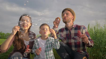 petite : happy family, little boy with mom and dad blowing soap bubbles during fun leisure on nature in field close up against sky