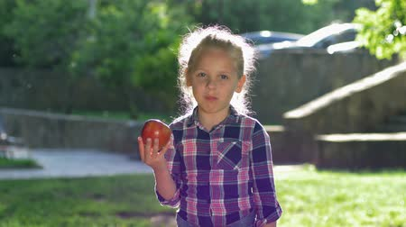 famished : happy little blonde girl bites and funny chew ripe juicy apple in backlight, kid dressed checkered shirt look on camera and smiles outdoors