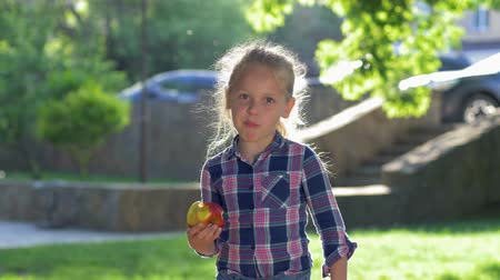 famished : healthy food, portrait of happy little blonde girl with beautiful eyes dressed plaid shirt chewing an juicy apple in the sunlight outdoor
