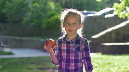famished : portrait of the eating child in backlight, little blonde girl chews ripe juicy apple and look on camera in open air Stock Footage