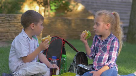 famished : schoolchildren eat sandwiches and talk during lunch time sitting on the lawn in schoolyard close up Stock Footage