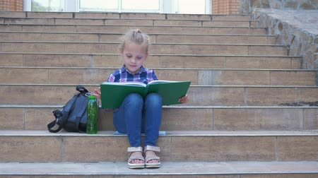 primeros pasos : pupil little girl reading a book sitting on the steps of the school next to a backpack during break Archivo de Video