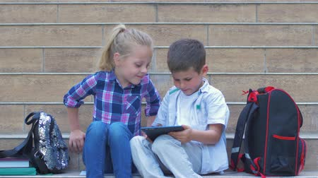 spolužák : schoolchildren a girl and boy use digital tablet sitting on school steps with backpacks in open air during break Dostupné videozáznamy