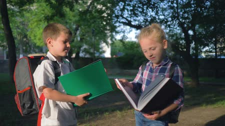 schoolbook : children education, schoolchildren boy and girl with big books in hands read after lessons standing in park