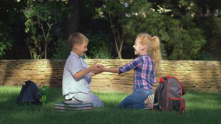 scholar : educational games, scholar girl and boy playing clapping game sitting on lawn in open air after schooling on school break