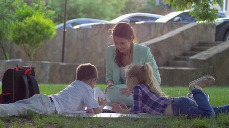 scholar : modern education, little children listening to woman reading fascinating book sitting on green grass in nature in sunny light close-up after school teaching Stock Footage