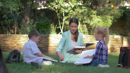 becario : modern education methods, classmate pupils boy and girl with tutor female read schoolbook and chat during lesson on lawn outdoors Archivo de Video