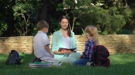 scholar : young teacher woman holds lesson outdoors for little boy and girl with books in hands while sitting on green grass